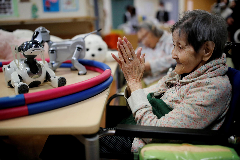 Một bà cụ vỗ tay gọi chó robot tại viện dưỡng lão Shintomi ở Tokyo, ngày 02/02/2018.