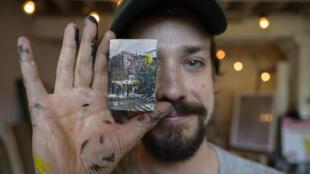 El artista Steve Wasterval posa para una foto con una mini pintura en su estudio de Greenpoint, en el distrito neoyorquino de Nueva York, el 25 de mayo de 2021. Luego la esconderá en el barrio para que los vecinos la encuentren