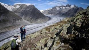 Des alpinistes se prennent en photo devant le glacier d'Aletsch au-dessus de Bettmeralp, dans les Alpes suisses, le 1er octobre 2019.
