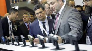 Le ministre brésilien de la Justice, Sergio Moro, regarde des armes au stand de l'entreprise Glock pendant le plus grand salon d'armement d'Amérique latine, à Rio de Janeiro, le 2 avril 2019.