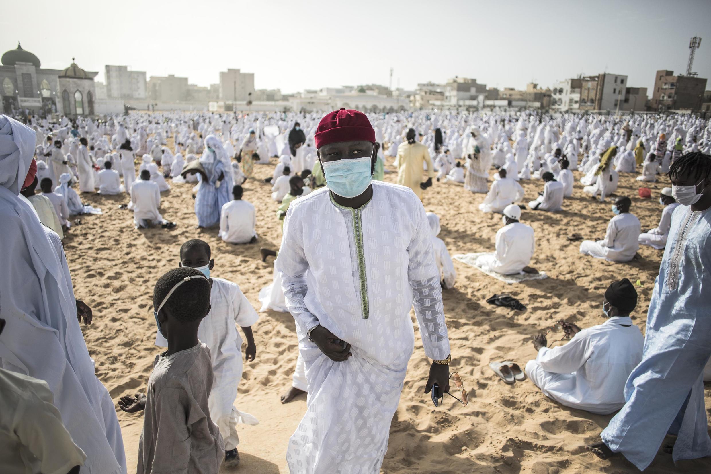 Un membre de la communauté Layene portant un masque quitte la plage devant la mosquée Yoff Layene, à la fin de la Korité, la fête pour la fin des 30 jours du jeûne du ramadan, à Dakar, au Sénégal, le 24 mai 2020.