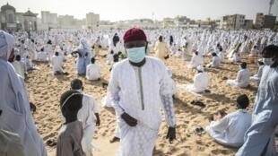 Un membre de la communauté Layene portant un masque quitte la plage devant la mosquée Yoff Layene, à la fin de la Korite, la fête pour la fin des 30 jours du jeûne du ramadan, à Dakar, au Sénégal, le 24 mai 2020.