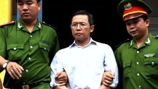 This file photo taken on August 10, 2011 shows French-Vietnamese blogger and lecturer Pham Minh Hoang (C) being led out from the courtroom at the Ho Chi Minh City People's Court House after he was jailed for three years for attempted subversion.
