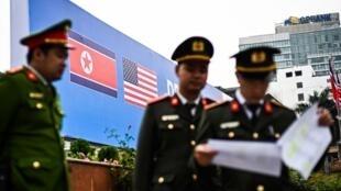 Maafisa wa polisi wa Vietinam jini Hanoi, Februari 24, 2019 mbele ya bendera za Korea Kaskazini na Marekani.