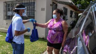 Los seis trabajadores reparten bolsas azules con mascarillas, sanitizadores, guantes y un folleto informativo.
