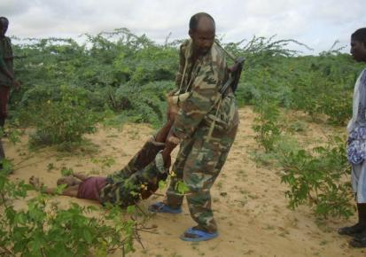 A Somali government soldier drags the dead body of an Islamic al-Shebab fighter killed during fighting between government and Islamist in southern Mogadishu
