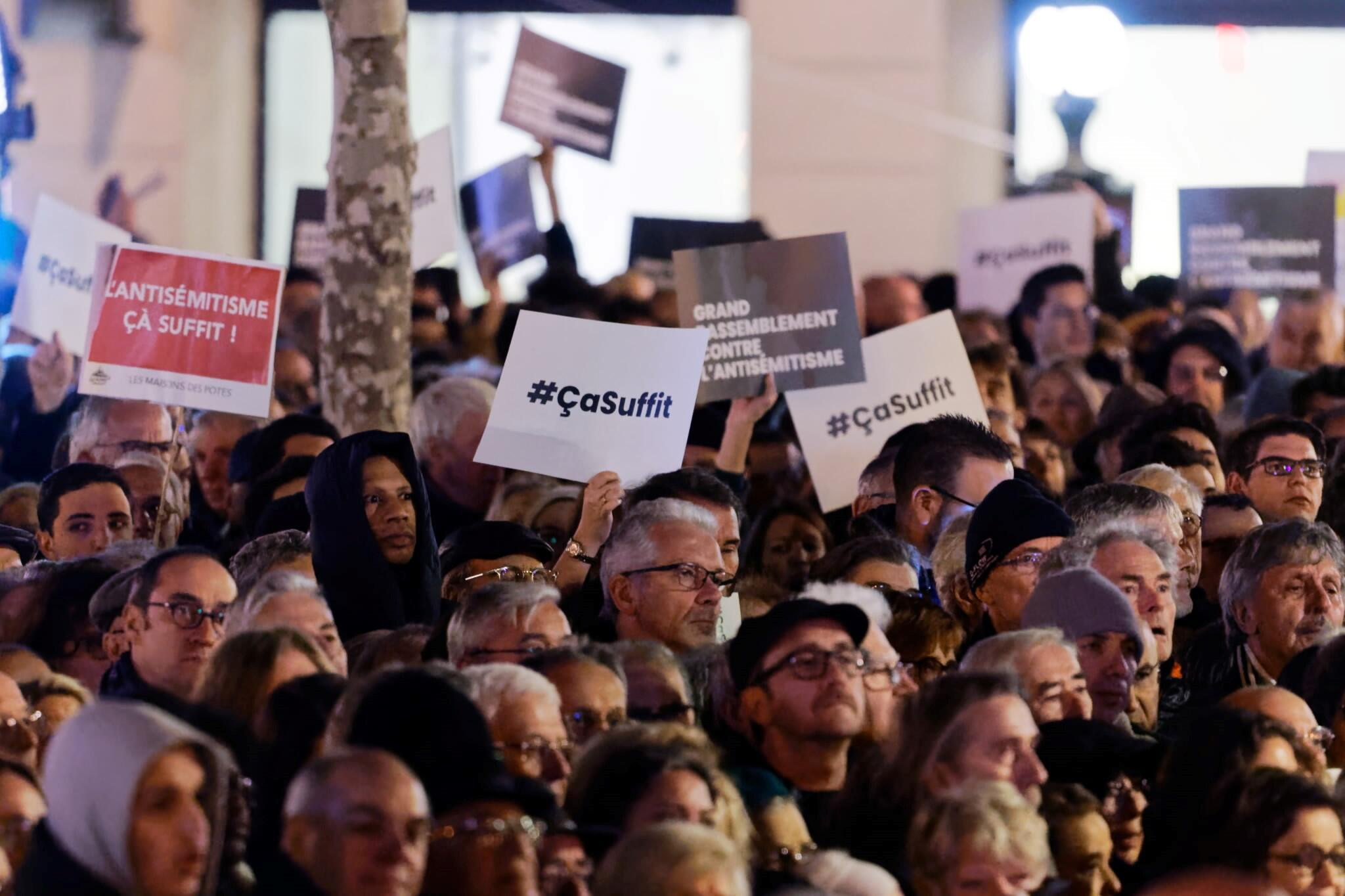 """Demonstrators hold placards reading """"ça suffit"""" – """"that's enough"""" – at a rally against anti-Semitism in Paris, February 2019."""