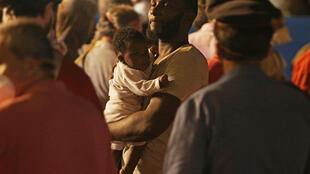 Un père et sa fille, débarquant à Palerme du navire suédois Poséidon, qui a secouru 570 personnes, et découvert les corps sans vie de 57 autres.