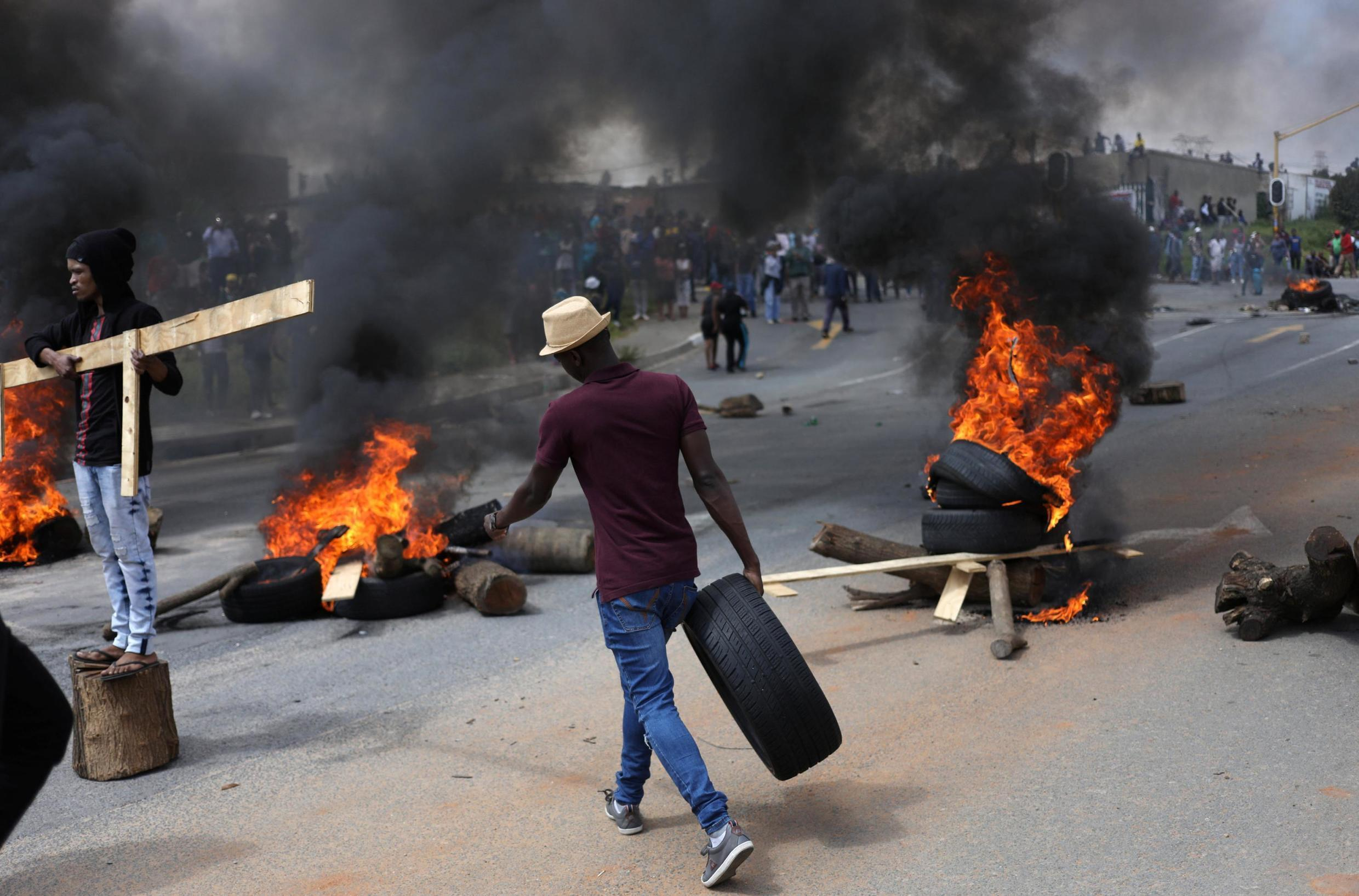 A man walks with a car tyre as he barricades the street during protesst in Alexandra township in the north of Johannesburg, South Africa