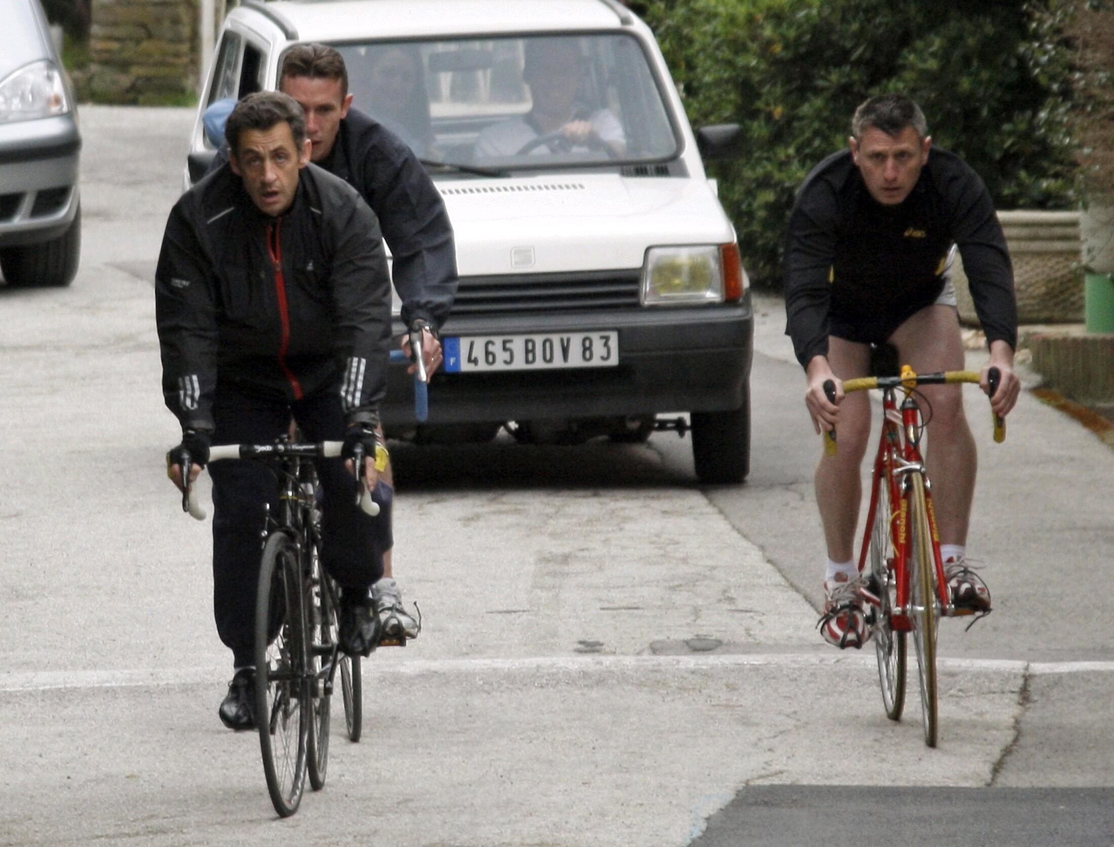 Уходящий президент Франции Николя Саркози совершает велосипедную проглуку в сопровождении телохранителей