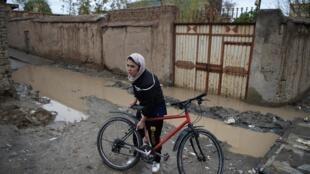 La cycliste afghane Kobra Samim avec son vélo dans une rue de Kaboul, le 14 avril 2019.