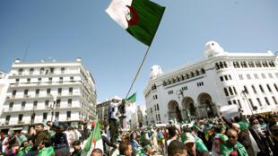 Manifestantes carregam bandeiras durante protestos pela saída do presidente Abdelaziz Bouteflika em Alger. Em 29 de março de 2019.