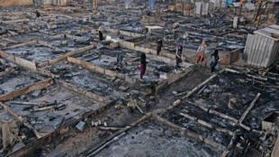 Des réfugiés syriens rassemblent leurs biens restants à Bhanine le 27 décembre 2020, après la mise à feu de leur campement par un clan libanais.