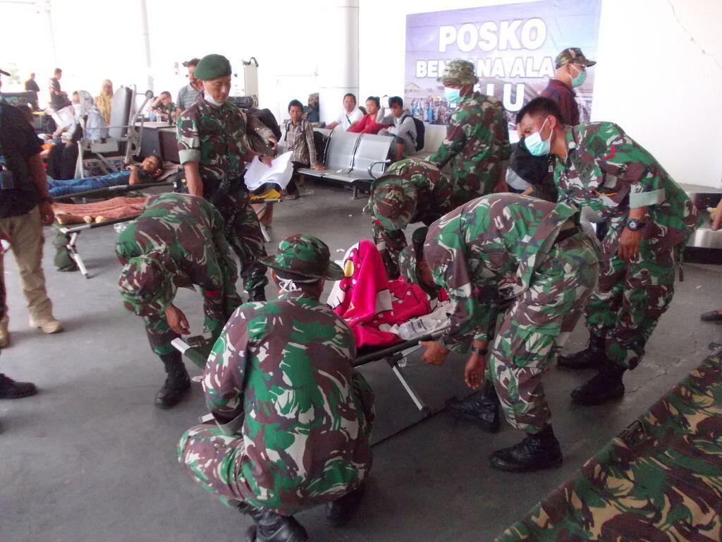 Des militaires portent assistance à un blessé à l'aéroport de Palu, le 2 octobre 2018.