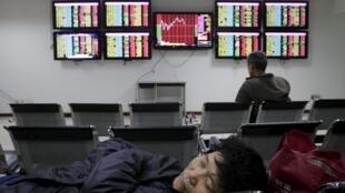 Một nhà đầu tư mệt mỏi nghỉ trưa trước các bảng chỉ số của một công ty chứng khoán ở Vũ Hán, 21/04/2015.