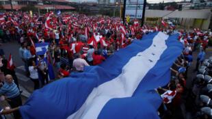 Manifestantes llevan una bandera de Honduras durante una protesta organizada por la oposición contra la reelección del presidente Hernández, el 6 de agosto de 2016 en Tegucigalpa.