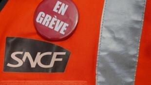 """A railworker wears a badge reading """"On strike""""."""