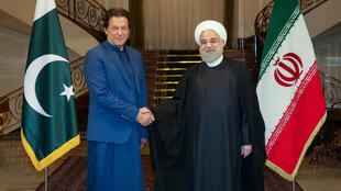 Iranian President Hassan Rouhani shakes hands with Pakistani Prime Minister Imran Khan in Tehran, Iran, October 13, 2019.
