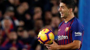 Le joueur du FC Barcelone Luis Suarez célèbre la fin de la rencontre face au Real Madrid, avec le ballon du match après avoir inscrit 3 buts au Camp Nou à Madrid, en Espagne, le 28 octobre 2018.