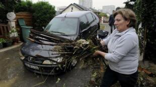 Francesa limpa detritos trazidos pela enchente que inundou a cidade de Nancy, nesta segunda-feira.