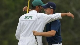 Jordan Spieth celebrates with his caddie Michael Greller after winning his first Major at the Masters