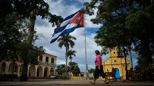 Una mujer con una máscara facial camina cerca de una bandera cubana en Viñales, provincia de Pinar del Río, Cuba, el 21 de julio de 2020
