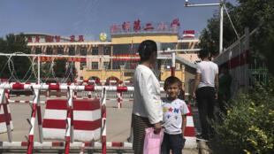 Ảnh chụp ngày 31/08/2018: một đứa trẻ và một người phụ nữ đứng đợi bên ngoài lối vào trường học được gắn camera giám sát và rào chắn, ở Peyzawat, vùng Tân Cương, miền tây Trung Quốc.