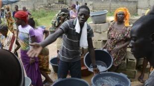 Des gens font la queue avec des seaux pour prendre un peu d'eau d'une source communale à Dakar, le 27 septembre 2013.