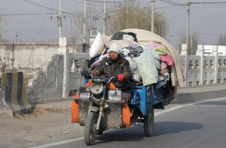 Một lao động nhập cư phải mang đồ đạc đi tìm nơi ở khác. Ảnh chụp tại Bắc Kinh ngày 25/11/2017.