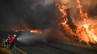 Bombeiros tentam conter a nova onda de incêndios em Portugal.