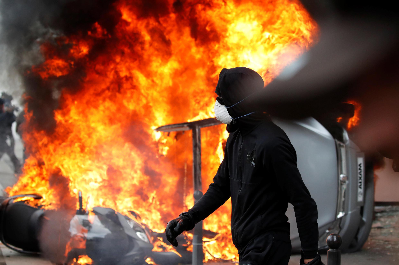 Un militant de la mouvance Black Bloc passe devant la voiture en flamme d'une concession Renault sacagée à paris.