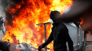 A masked protester walks near a car that burns outside a Renault automobile garage during clashes during the May Day labour union march in Paris, France, May 1, 2018.