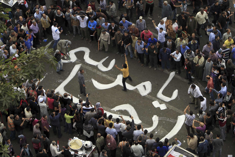 """Manifestantes escrevem no chão: """"Morsi, vá embora""""."""