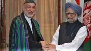 Hamid Karzai (L) shakes hands with Manmohan Singh at Hyderabad House in New Delhi