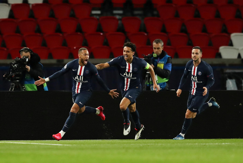 Le Brésilien Neymar (à gauche) fête son but face au Borussia Dortmund, en huitième de finale retour de la Ligue des champions, devant les tribunes du Parc des Princes vides à cause du Coronavirus.