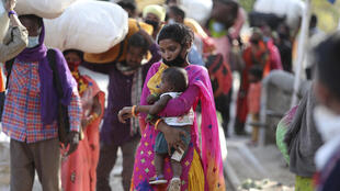 A woman holds a child and waits with other migrant workers outside a railway station hoping to be able to travel to their home states, in Jammu, India, Friday, May 22, 2020.