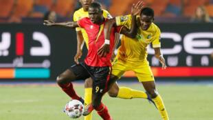 L'Ougandais Patrick Kaddu à la lutte avec deux joueurs zimbabwéens le 26 juin 2019.