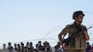 Un soldat turc monte la garde avec derrière lui des Kurdes syriens qui attendent derrière des barbelés, près de la ville de Suruc, le 21 septembre 2014.