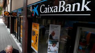 A man walks past a Caixa bank branch in Barcelona, Spain October 6, 2017.