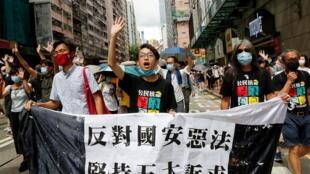(Từ trái sang) : Dân biểu Chu Khải Địch (Eddie Chu Hoi Dick), phó chủ tịch Mặt trận Nhân dân về Nhân quyền Trần Hạo Hoàn (Figo Chan) và nhà hoạt động Lương Quốc Hùng (Leung Kwok Hung) tuần hành nhân ngày kỷ niệm Anh trao trả Hồng Kông cho Trung Quốc, 01/07/2020.