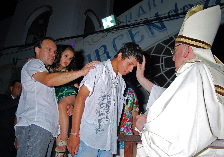 Jorge Mario Bergoglio bendiciendo habitantes de la Villa 21, en el barrio de Barracas, en diciembre de 2012.