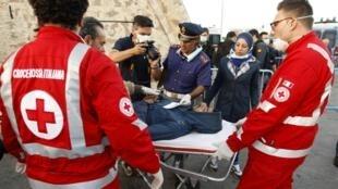 Polícia italiana carrega o corpo de um dos imigrantes mortos na praia de Catania