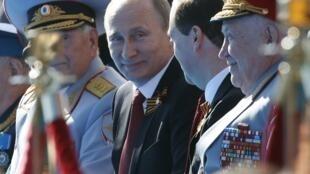 Владимир Путин разговаривает с Дмитрием Медведевым перед началом военного парада на Красной площади 9 мая 2014, Москва
