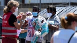 Une personne apportant des produits de première nécessité à des personnes sous quarantaine à leur domicile après une épidémie de coronavirus dans un abattoir de la société Toennies le 23 juin 2020 à Verl, dans l'ouest de l'Allemagne.