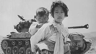 A young girl with her brother on her back walks past a stalled M-26 tank at Haengju, Korea in June 1951