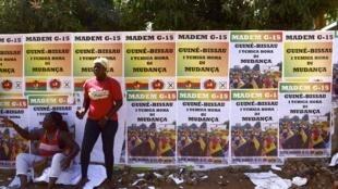 Des femmes devant un mur couvert d'affiches électorales du Madem-G15, le 8 mars 2019.