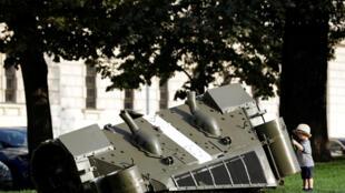 """Một em bé trước tác phẩm của nghệ sĩ David Cerny nhằm kỷ niệm 50 năm """"Mùa Xuân Praha"""", khi xe tăng Liên Xô tràn vào thủ đô Tiệp Khắc. Ảnh chụp ngày 21/08/2018."""