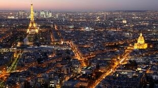 Paris with the illuminated Eiffel Tower (L), the Hotel des Invalides (R) and rooftops at night.