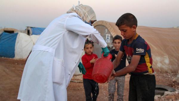 Un médecin syrien vient en aide à des enfants au camp de Dana, à la frontière entre la Turquie et la Syrie, le 26 juillet 2020