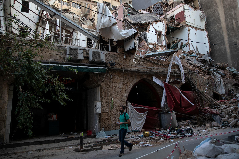 Homem passa diante de residências destruídas pela explosão de 4 de agosto no porto de Beirute. Ainda se recuperando da tragédia, população enfrenta novo lockdown a partir desta sexta-feira (21).